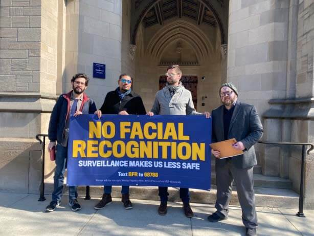 Facial recognition protesters hold up a banner.