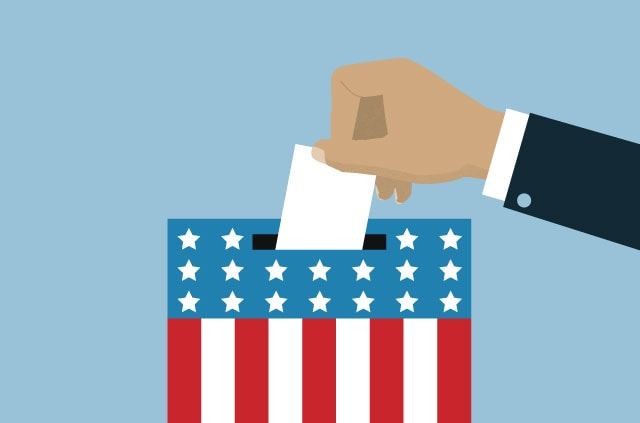 Hand putting a ballot in a box with the U.S. flag on it.