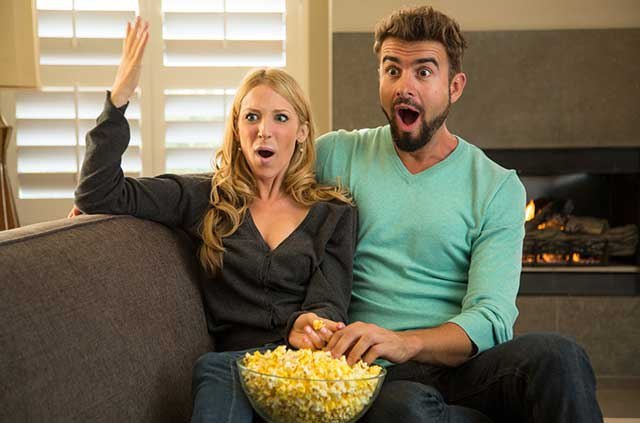 Couple on couch watching Netflix and sharing a bowl of popcorn.