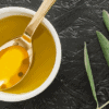 Bowl of olive oil with a spoon & an olive branch beside it.