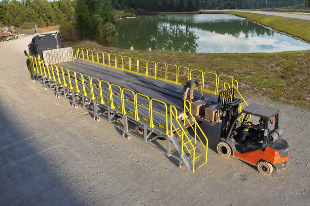 Worker standing on custom rolling platform for flatbed truck outdoors by pond