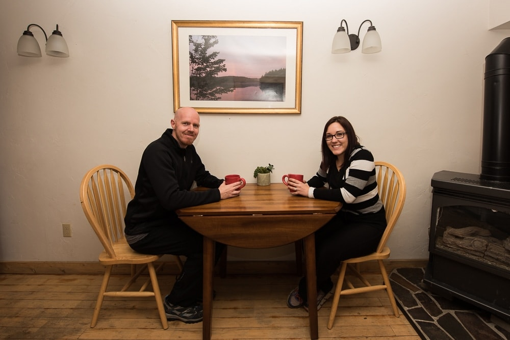 Brooke and Buddy sitting at the table while sipping coffee at their Grand Lake Cabin Rental