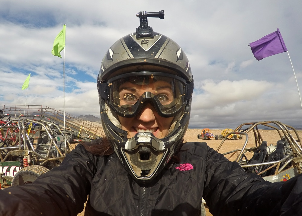 Brooke taking a selfie in a helmet and goggles with mud on them from our dune buggy chase outside the las vegas strip