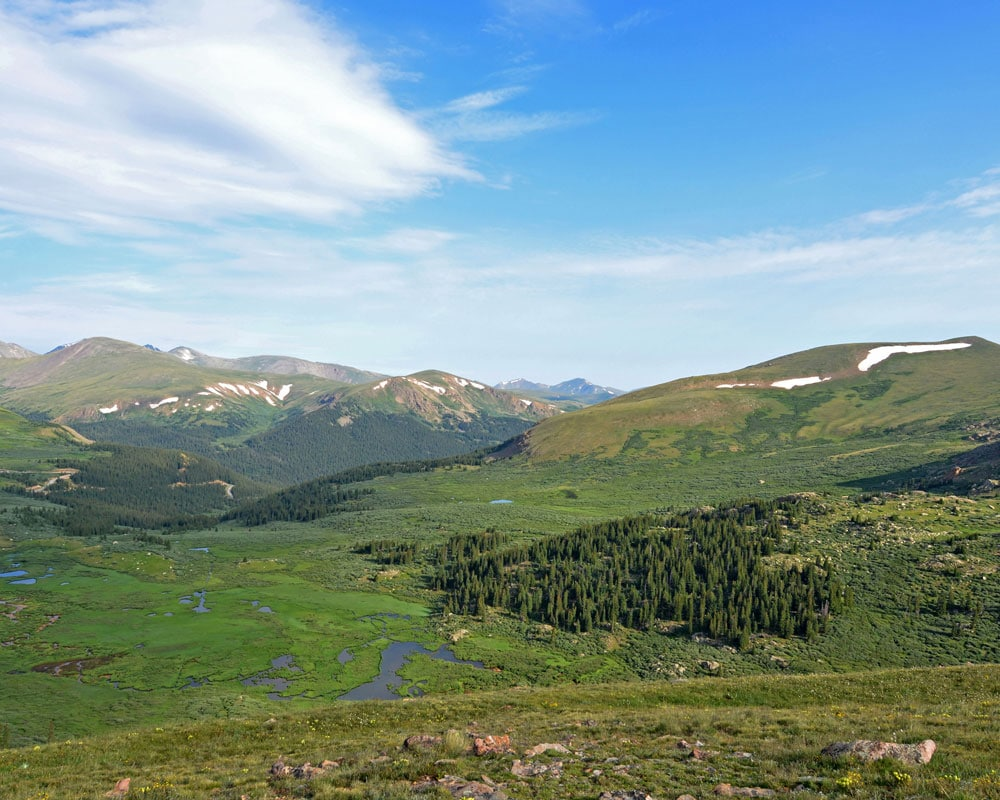 View into the valley full of green while hiking Mt. Bierstadt