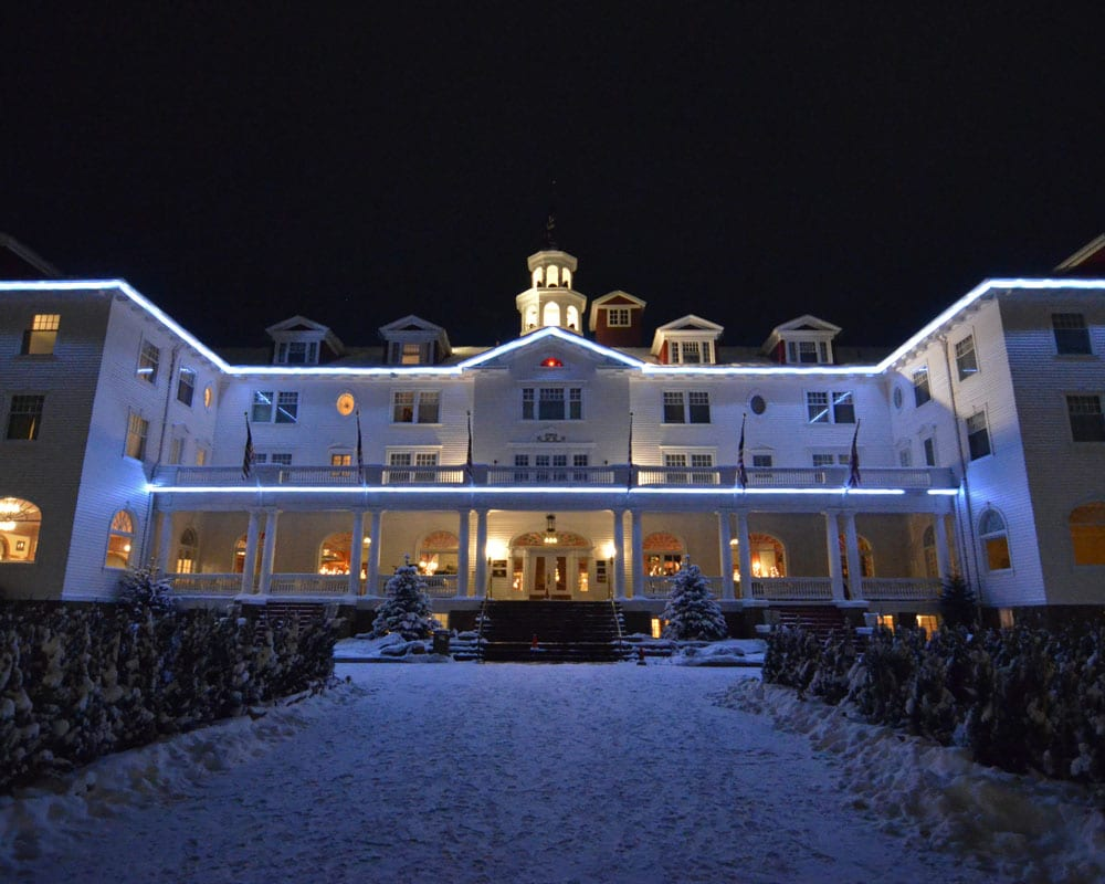 Outside of the Stanley Hotel in winter with snow on the ground.