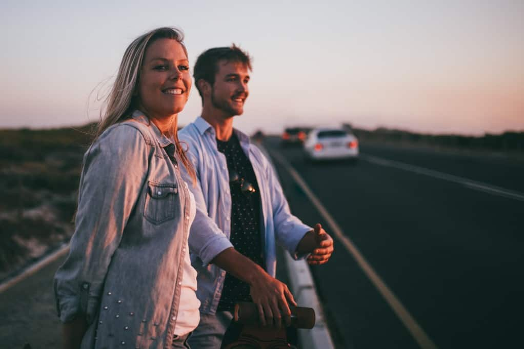 romantic couple smiling by a road