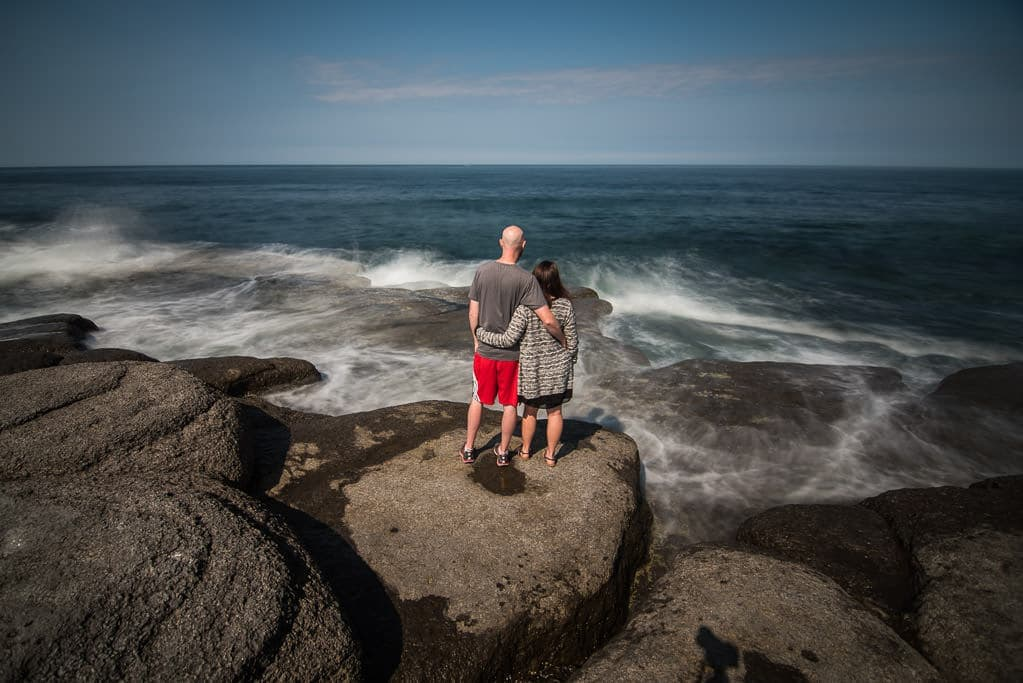 Brooke and Buddy standing side by side watching waves crash in front of them at Point Riche Lighthouse