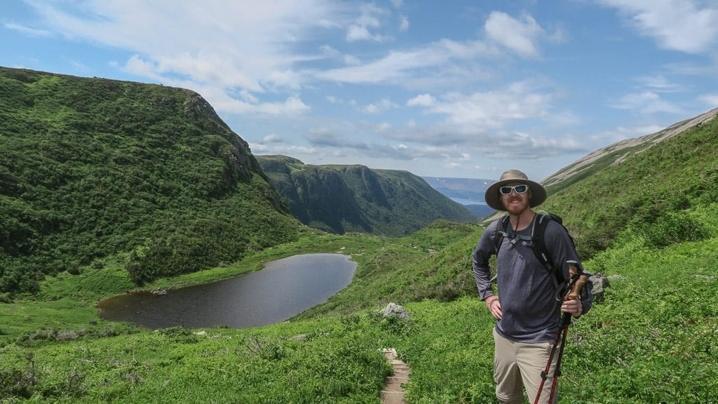 Buddy posing next to the narrow trail surrounded by grass near a beautiful lake in Gros Morne National Park