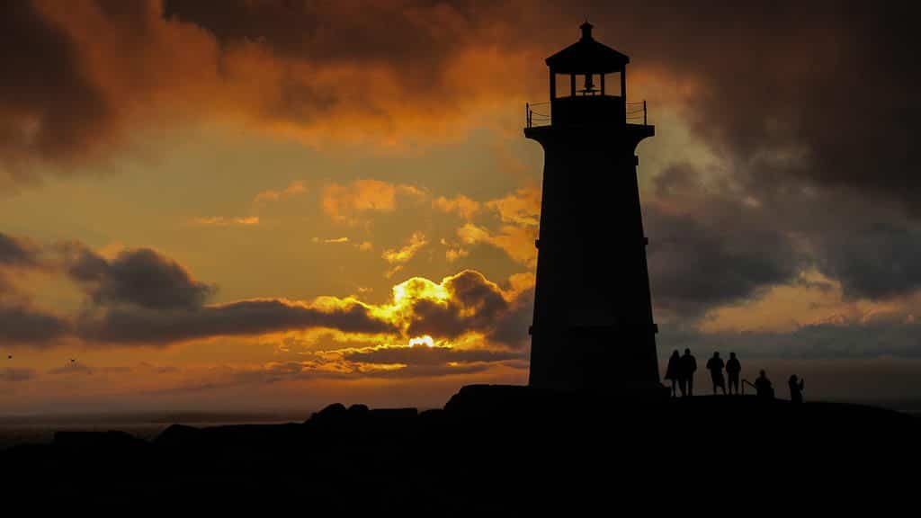 Sunset at Peggy's Cove Lighthouse in Nova Scotia with people standing next to the lighthouse