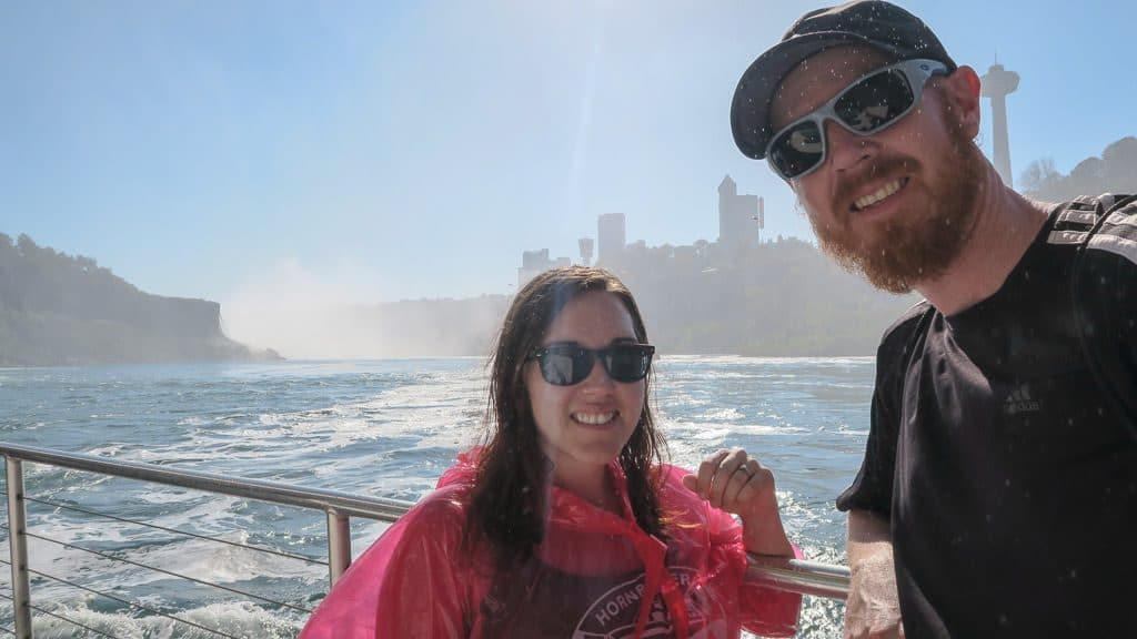 Brooke and Buddy posing on the Hornblower Niagara Cruise, one of the top things to do in Niagara Falls