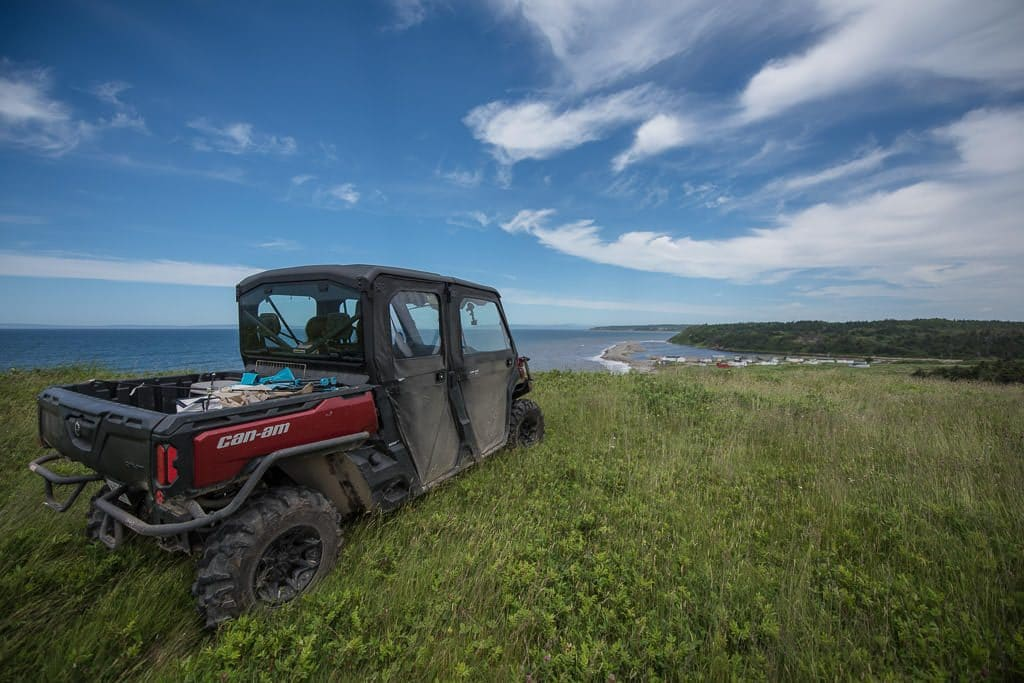 Newfoundland ATV sitting in high grass on the top of a hill overlooking the coast.