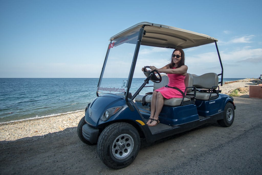 Brooke driving the Golf cart in Avalon in her bright pink dress.