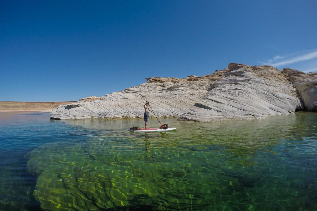 Buddy Paddleboarding on the clear water of Lake Powell next to a rock and you can see in the water 40 feet under him