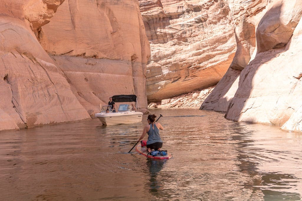 Brooke on her paddleboard on her knees as a boat passes by in the canyon