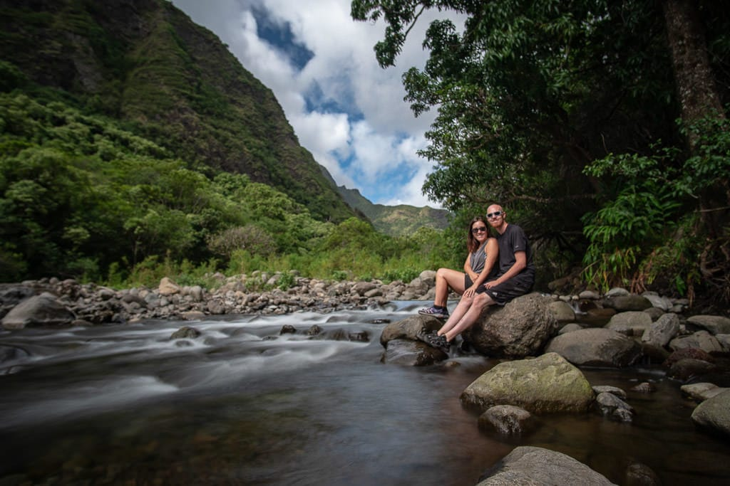 Brooke and Buddy sitting on a rock together next to the river in Iao Valley State Park