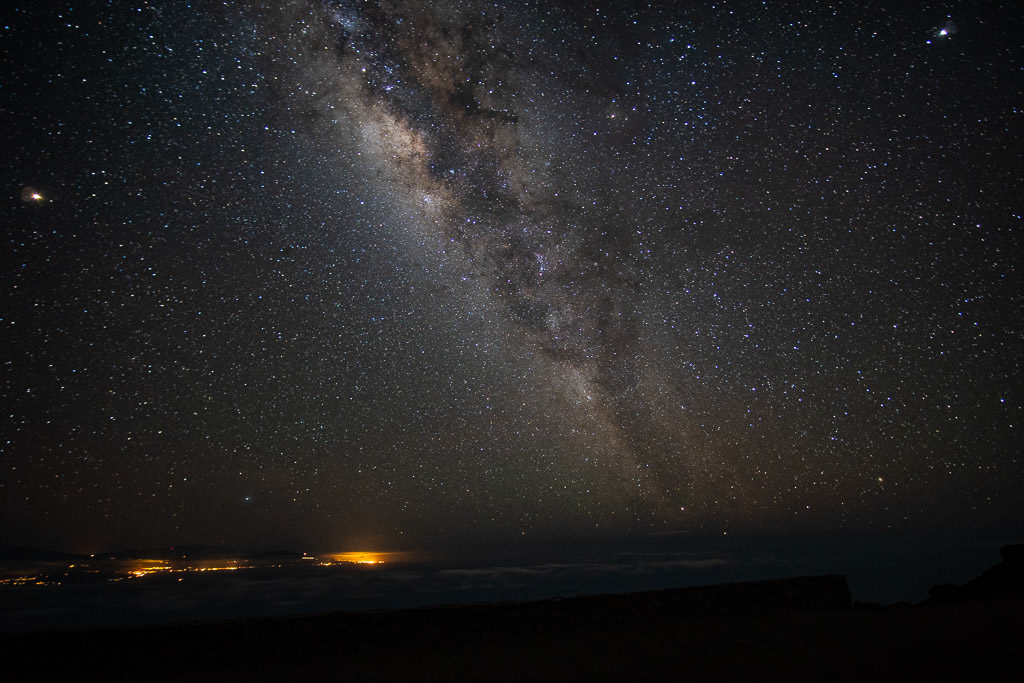 Milky Way and stairs with city lights in the distance from the Haleakala summit