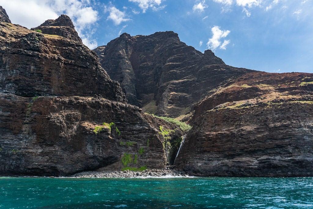 mini waterfall with scenic views on napali coast boat tour in Kauai