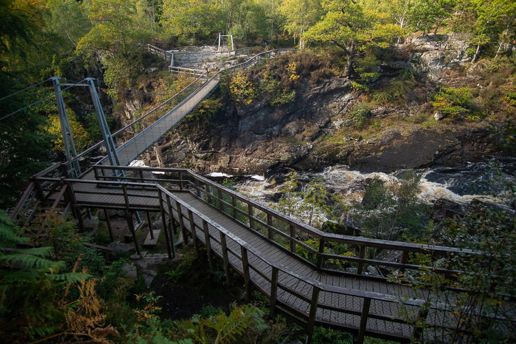 The bridge and pathway that leads to a gorgeous overlook looking down onto Rogie Falls in Scotland