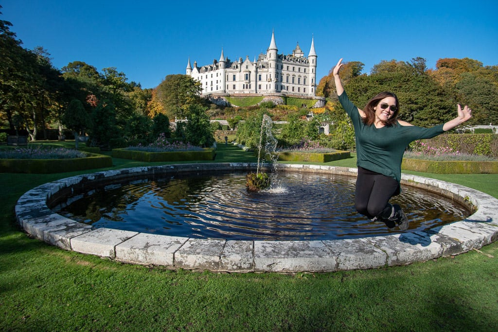 Brooke jumping in the air near one of the fountains in the garden with the huge Dunrobin Castle in the background