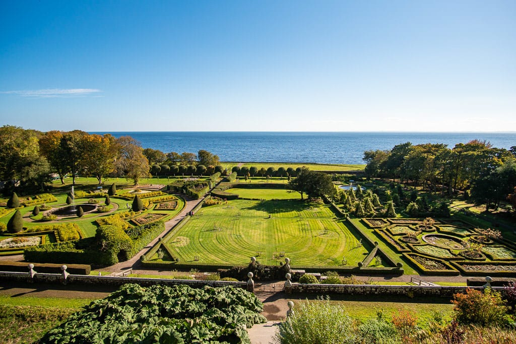 The amazing and beautiful manicured garden at Dunrobin Castle with the sea off in the distance right behind the property