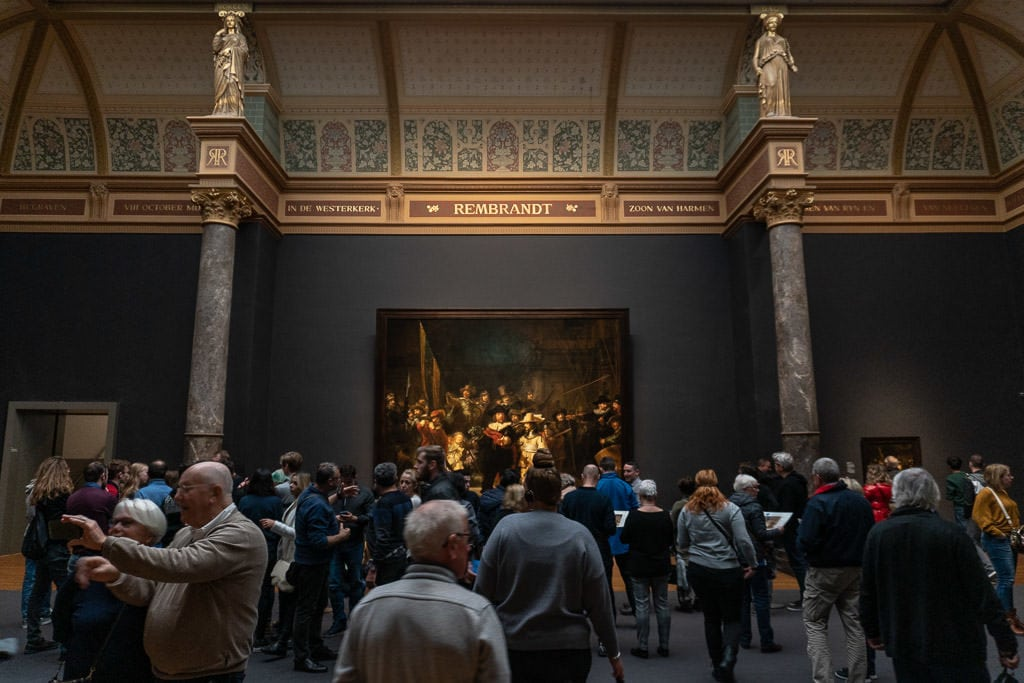 crowds looking at a large Rembrandt 'Night Watch' painting at Rijksmuseum in amsterdam