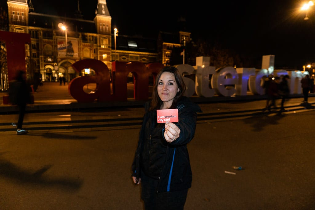 Brooke holding the i amsterdam city card in front of I amsterdam sign at night