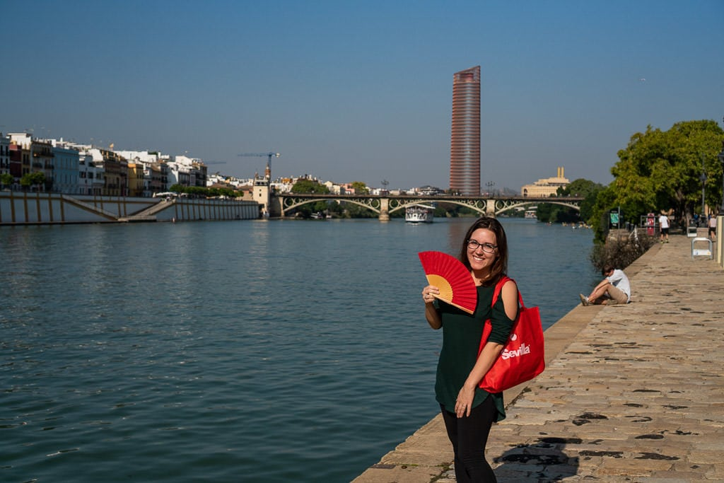 posing with red fan on hot day next to the river in sevilla spain