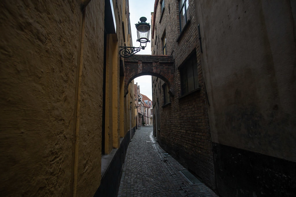 side street and arch in bruges belgium