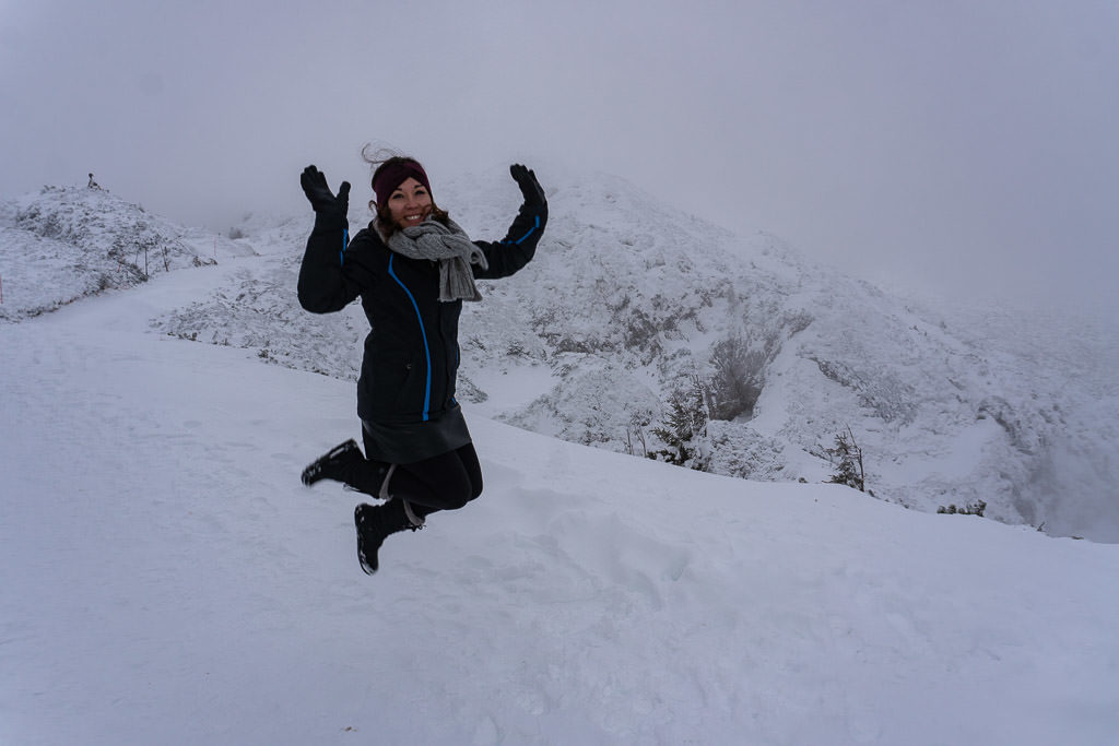 jumping for joy with scenic salzburg austria views on mountain atop Untersberg cable car