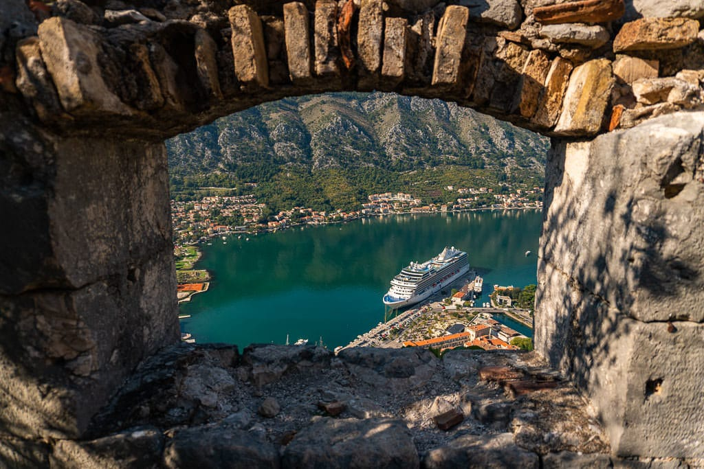 View from one of the Fortress windows looking out into Kotor Bay at a cruise ship that is docked for the day.
