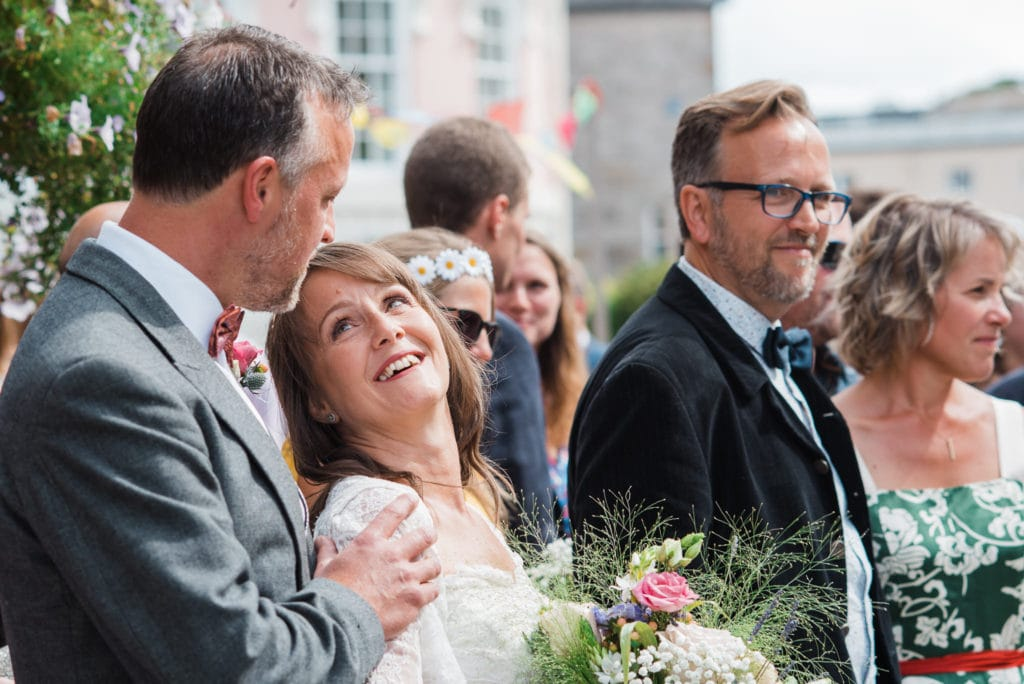 Bride and groom look lovingly into each others eyes surrounded by family and friends