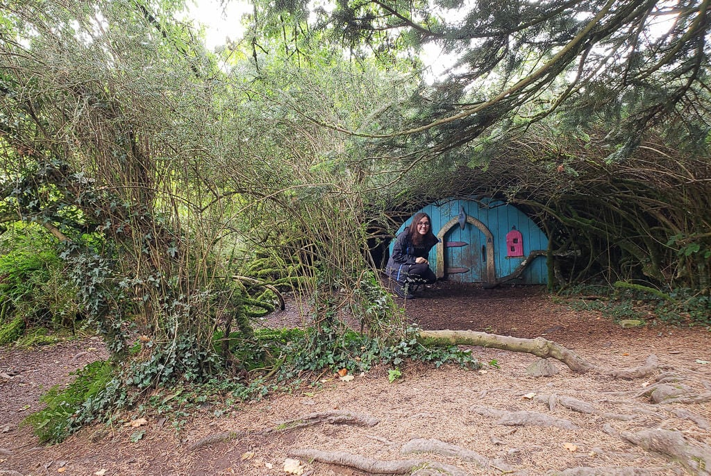 Brooke next to a tiny little house in the bushes at Giant's Lair Story Trail at Slieve Gullion Forest Park