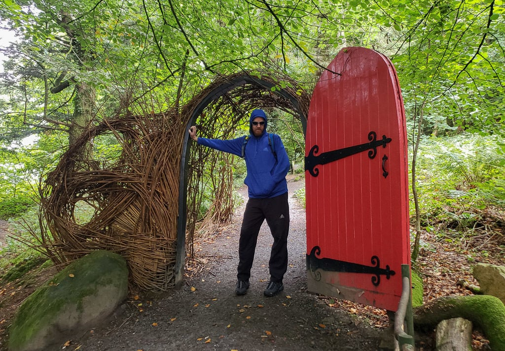Buddy next to a giant red door that you walk through during part of the Giant's Lair Story Trail at Slieve Gullion Forest Park