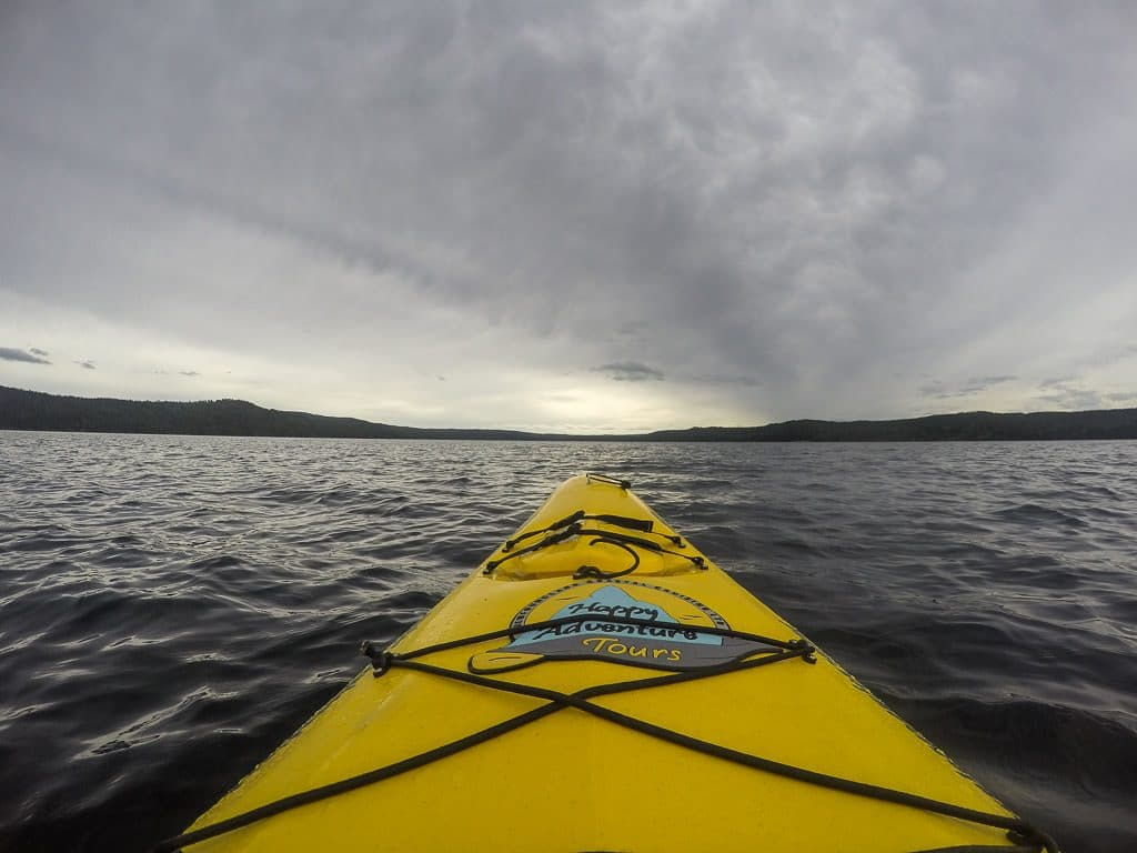 Front of the kayak in the open ocean with the Happy Adventure Tours logo