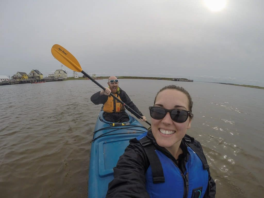 Brooke smiling and taking a selfie while Buddy paddles while kayaking