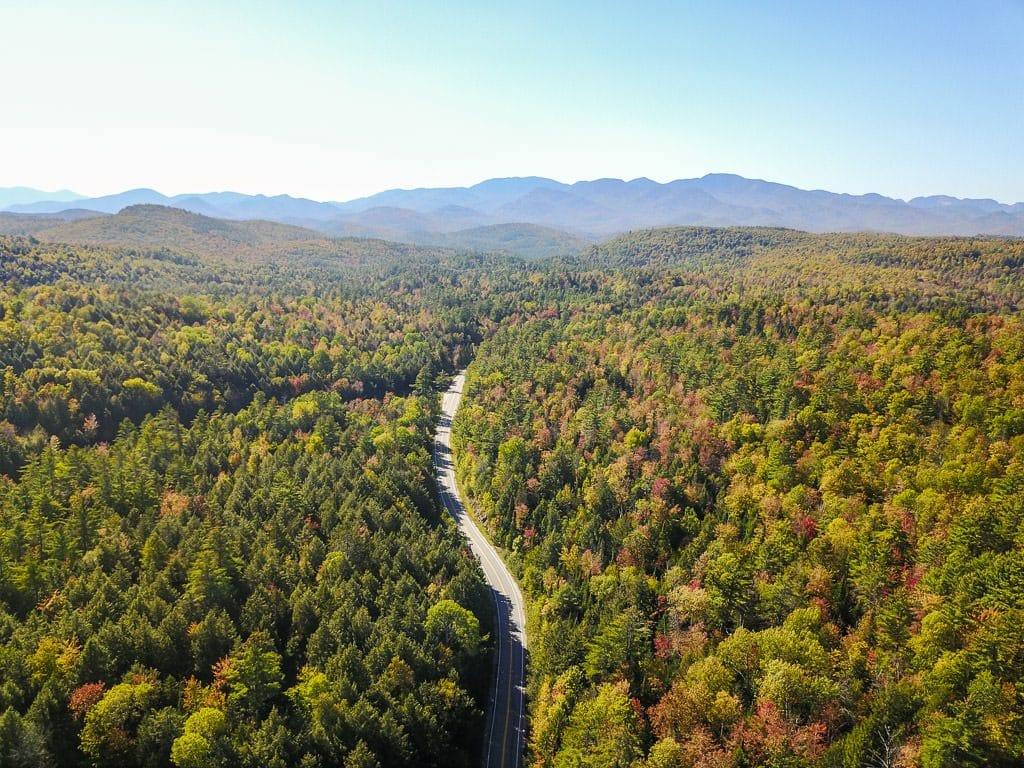 Drone shot of the road surrounded by bright trees with the vermont mountains in the background