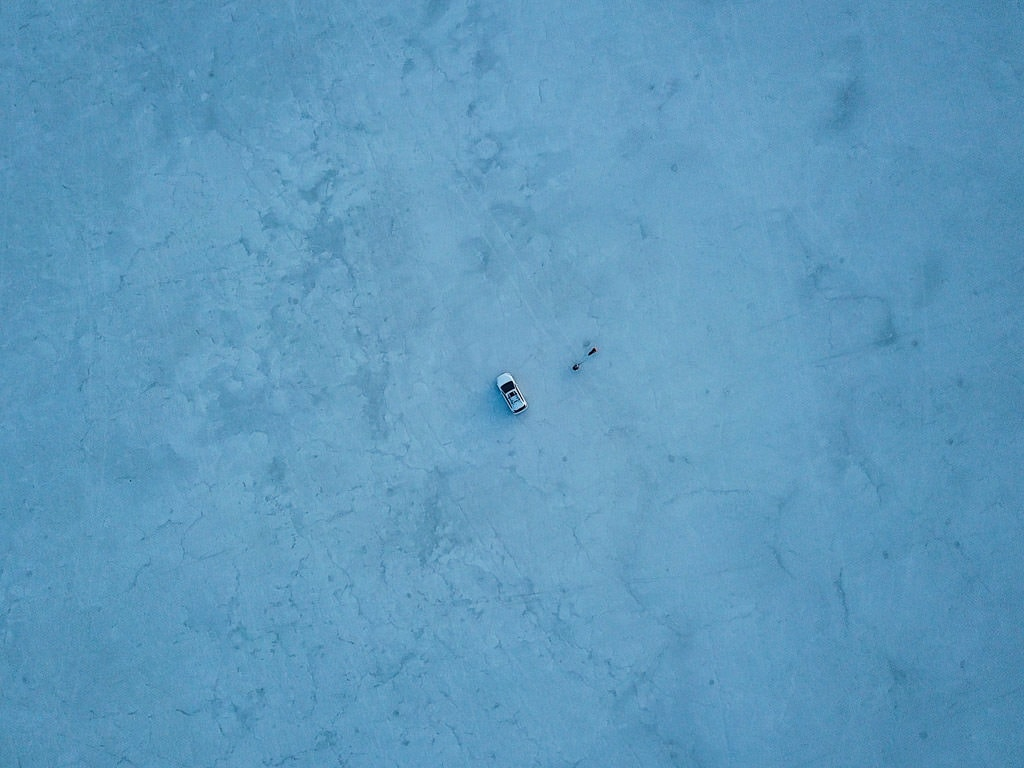 Aerial photo of Brooke and Buddy standing outside of the car on the Bonneville Salt Flats