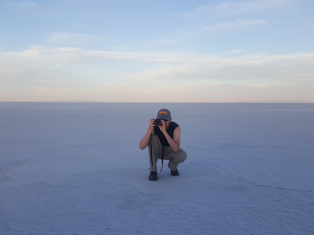 Buddy kneeling down and taking photos at the Bonneville Salt Flats during dusk