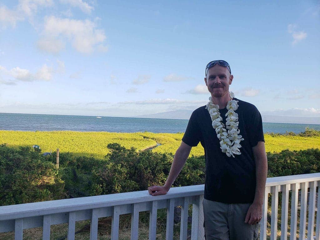 standing on porch at our house sit in molokai wearing a hand-made lei from homeowners