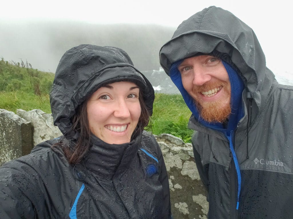 Brooke and Buddy next to the Cliffs of Moher in all their rain gear