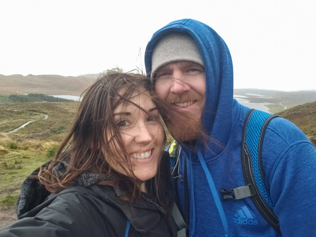 Brooke and Buddy taking a photo in the Isle of Skye on a very windy day