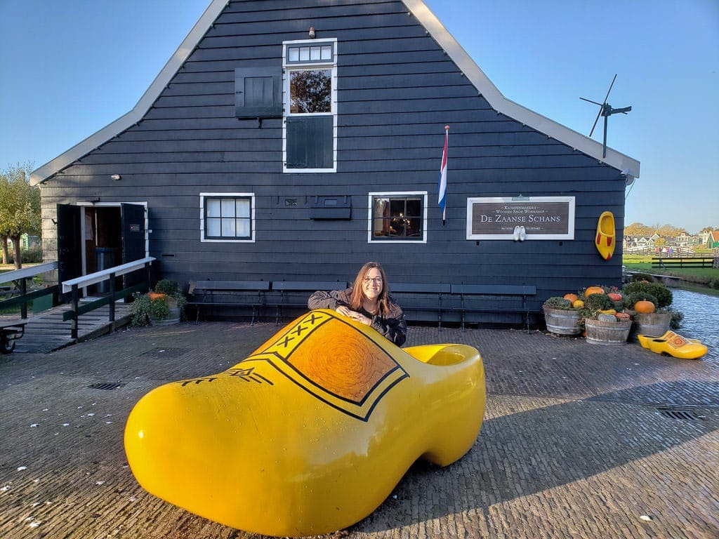 posing in a dutch wooden shoe during zaanse shans day trip from amsterdam to holland's countryside