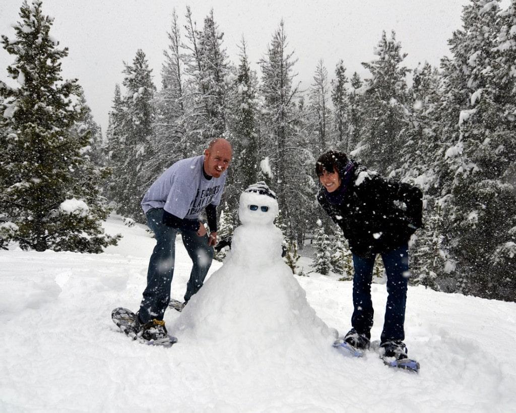 Brooke and Buddy building a snowman in Rocky Mountain National Park in May during their honeymoon and first visit to Colorado