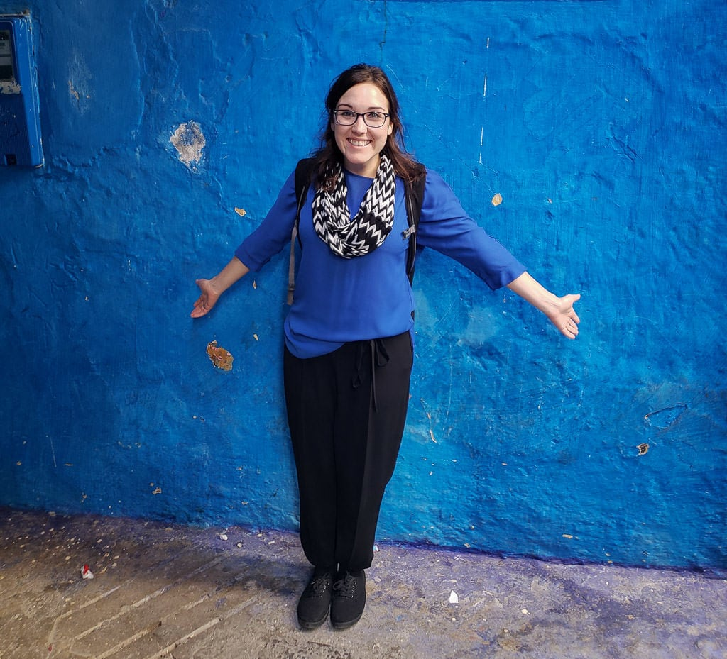 in front of bright blue wall in tangeir on day trip to Morocco