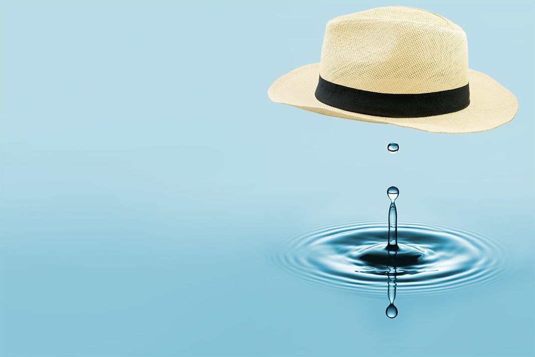 Straw fedora above a drop of water.