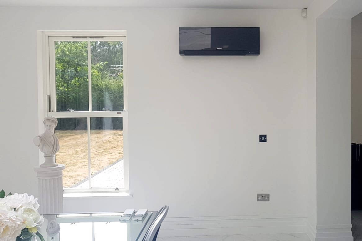 Black mitsubishi electric wall mounted air conditioning unit in living space by dining table and window fitted by SubCoolFM