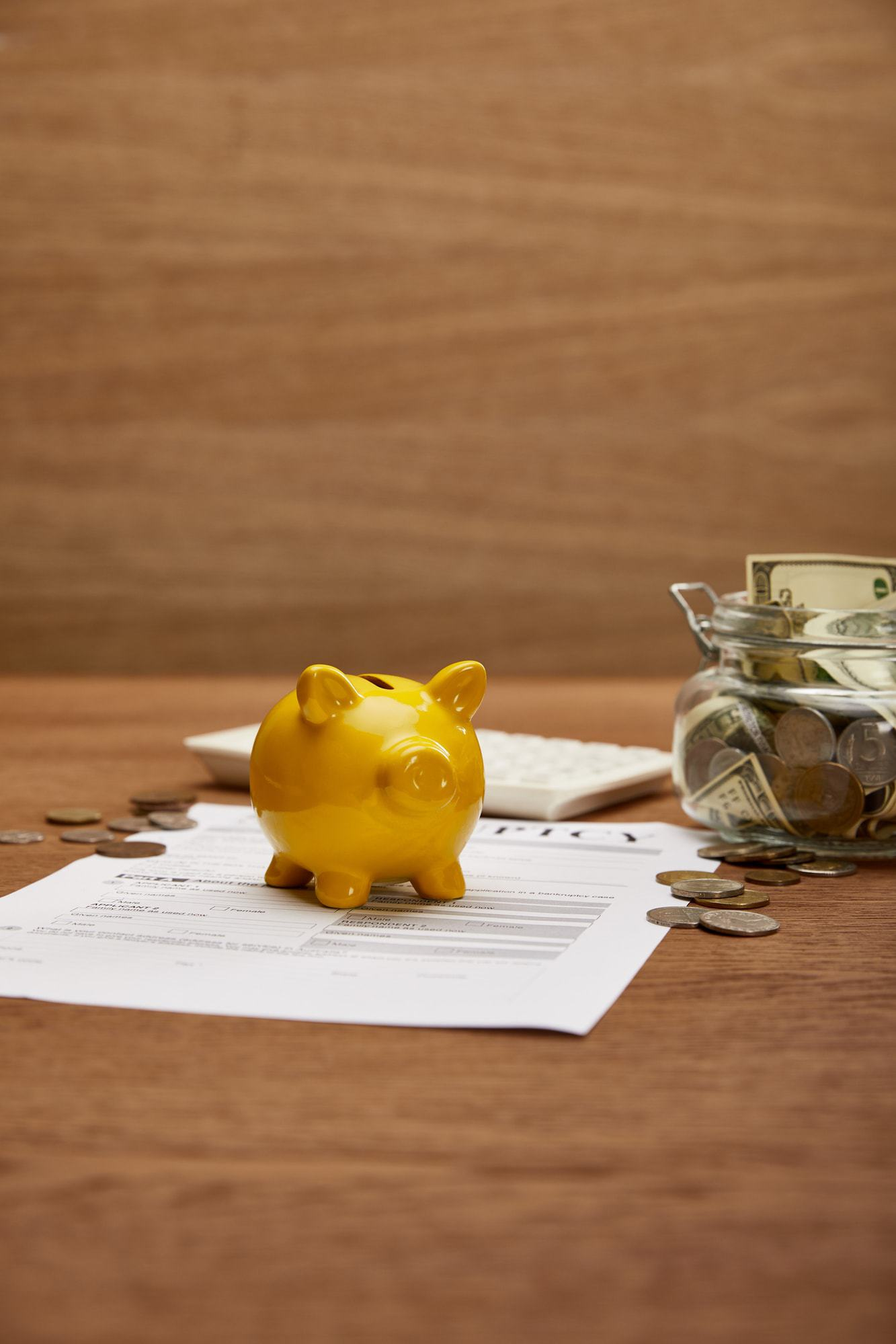 Yellow pigy bank sitting on bankruptcy paperwork with a jar of dollar bills