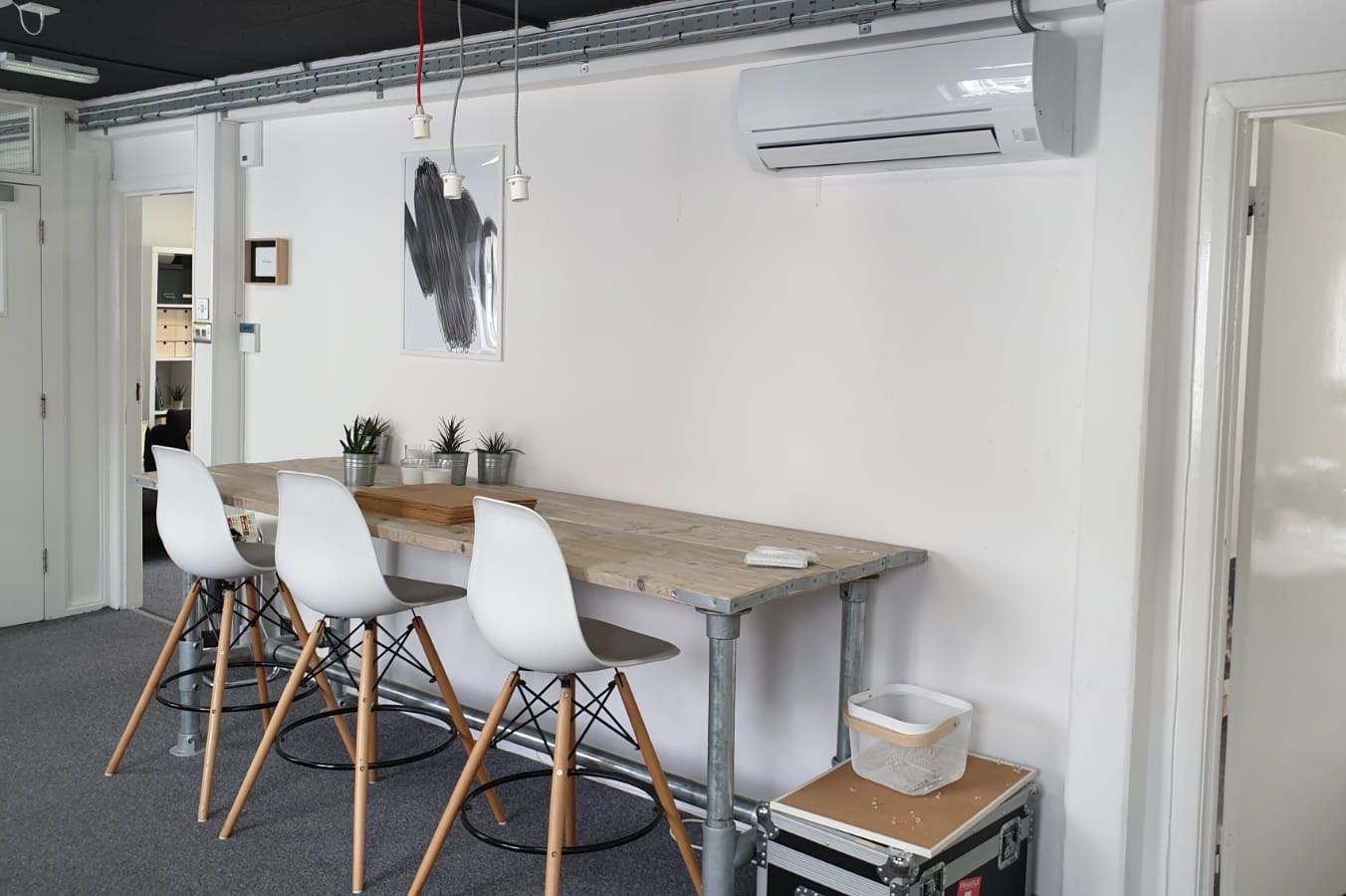White wall mounted commercial air conditioning unit in Brighton offices over casual seating area fitted by SubCool FM