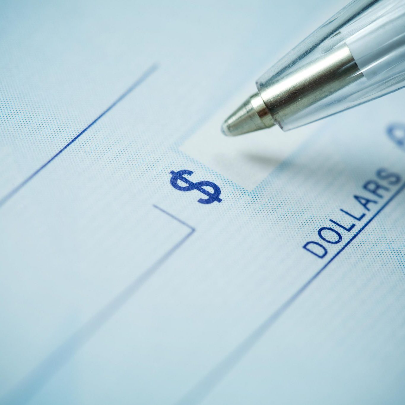 Close up of a pen and blank check.