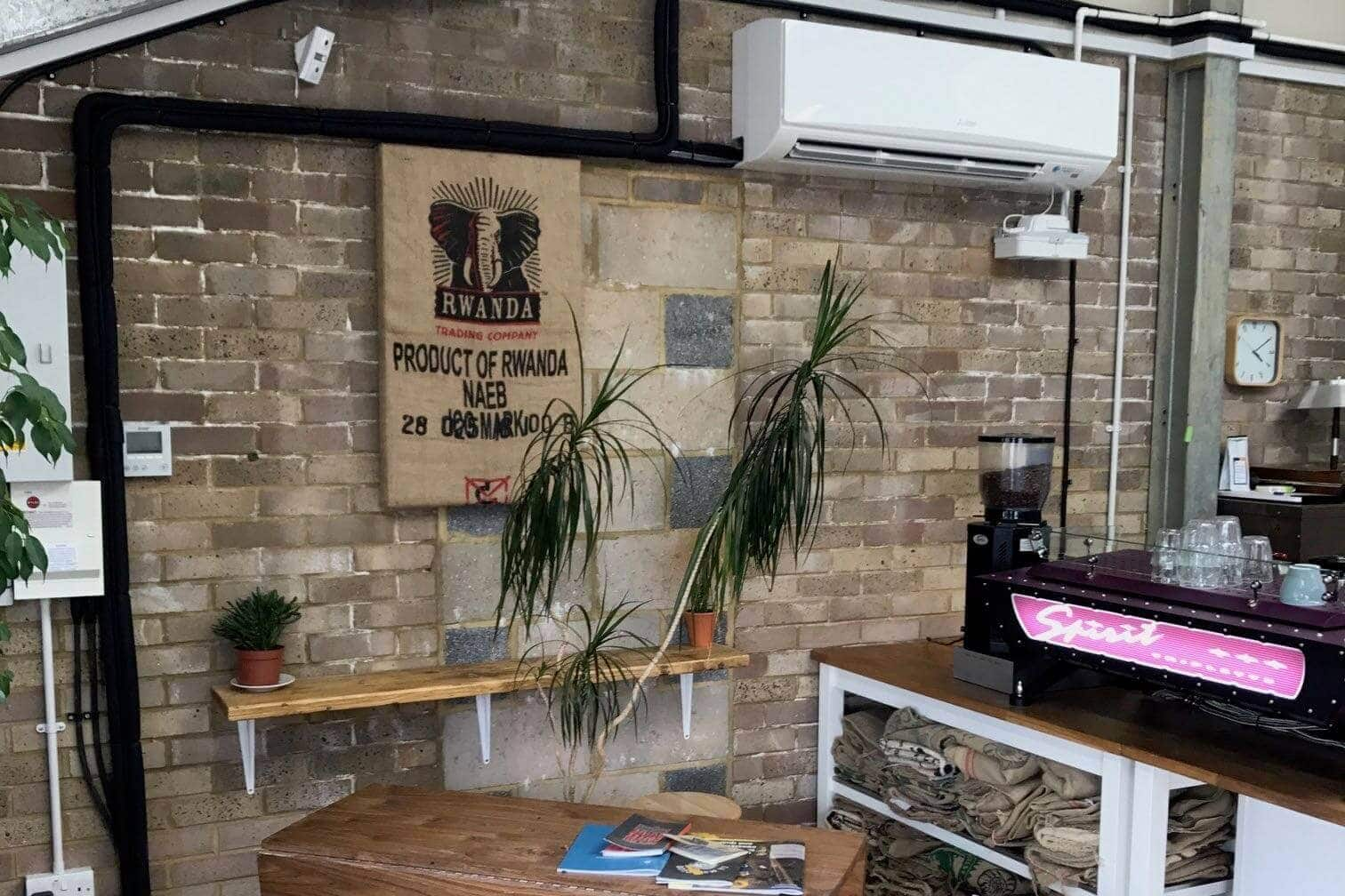 White commercial wall mounted mitsubishi air conditioning unit in Horsham coffee roaster by SubCoolFM